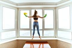 苗条妇女洗涤窗口 免版税库存照片