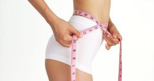 苗条妇女测量的腰部侧视图  库存图片