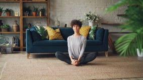 苗条少妇今后弯曲到在家然后放松在补鞋匠` s姿势的一条腿在瑜伽实践期间 健康 股票视频