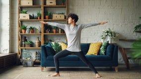 苗条少妇在家实践站立在战士位置开发的力量和毅力的瑜伽 顶楼样式 股票视频