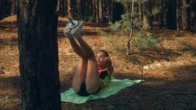 苗条热的女孩提起了她的腿,并且震动压入森林 股票录像