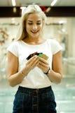 苗条金发碧眼的女人是愉快的,整理银行卡 库存图片