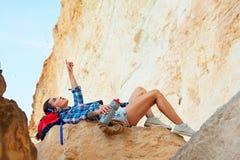 苗条登山人放下休息在峭壁顶部 免版税库存图片