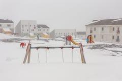 苛刻的格陵兰在雪盖的童年、操场和冰 图库摄影