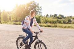 英俊与有时髦发型佩带的衬衣和的牛仔裤在后面骑马自行车的背包在享用镇静大气厕所的路 免版税库存图片