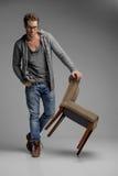 英俊与椅子。倾斜在Th的玻璃的英俊的年轻人 免版税图库摄影