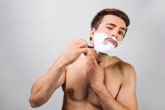 英俊和可爱的人是在刮他的胡子的过程af中 他doesn ` t遗憾对此 真正这个人用途 图库摄影