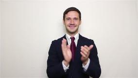 英俊年轻商人微笑和有效地拍的手,招呼新的顾客 股票录像