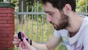 英俊男士在篱芭旁边打开有婚戒的小蓝色天鹅绒箱子 影视素材