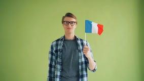 英俊男士的慢动作有看照相机和微笑的法国旗子的 影视素材