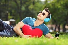 英俊男性说谎在与红色心脏听的音乐的一棵草 免版税库存照片