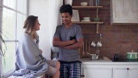 英俊的不同种族的夫妇谈话在厨房里早晨 可爱的女孩坐被盖的窗口基石 影视素材