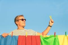 年轻英俊的与晒衣夹的行家人垂悬的洗衣店 免版税图库摄影