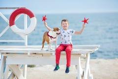 英俊的与他的朋友牛头犬一起的男孩青少年的happyly消费的时间在海边举行演奏的孩子狗两个海星紧密t 库存照片
