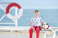 英俊的与他的朋友牛头犬一起的男孩青少年的happyly消费的时间在海边举行演奏的孩子狗两个海星紧密t 免版税库存照片