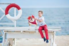 英俊的与他的朋友牛头犬一起的男孩青少年的happyly消费的时间在海边举行演奏的孩子狗两个海星紧密t 图库摄影