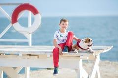 英俊的与他的朋友牛头犬一起的男孩青少年的happyly消费的时间在海边举行演奏的孩子狗两个海星紧密t 免版税库存图片