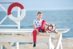 英俊的与他的朋友牛头犬一起的男孩青少年的happyly消费的时间在海边举行演奏的孩子狗两个海星紧密t 库存图片