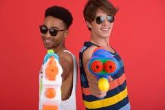英俊的两个人朋友用水戏弄枪 库存图片