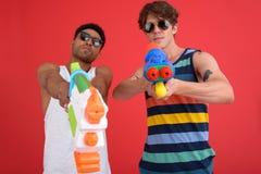 英俊的两个人朋友用水戏弄枪 免版税库存照片