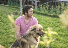 英俊的亚裔人和他的蓬松狗在一个晴天在庭院里 免版税库存照片
