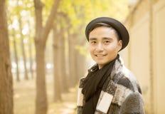 英俊的亚裔人在秋天公园微笑 免版税库存照片