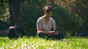 英俊的亚裔人坐在sunlights的草并且移动他的电话,被聚焦的,都市看法,学习震动 股票视频