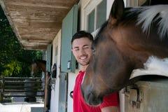 英俊的人、男性与胡子和马车手与红色衬衣宠爱他的马在他槽枥他的农场的 库存照片