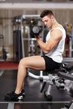英俊的人与在健身房的重的哑铃一起使用 库存照片