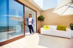 英俊的人享有在屋顶大阳台的生活,与露天场所厨房和滚滑门 免版税库存图片