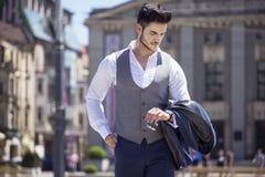 英俊的人优美穿戴了看他的手表 免版税库存照片