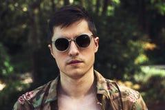 英俊的人佩带的太阳镜和T恤杉暑假 免版税库存照片