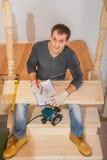 年轻英俊的人佩带的工作服坐梯子   库存照片