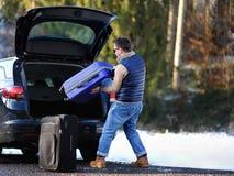 英俊的人去的假期,装载他的汽车起动带着手提箱 图库摄影