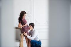 英俊的人听他美好怀孕妻子` s肚子和微笑 免版税库存图片