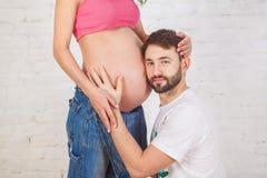 英俊的人听他美丽的怀孕的妻子` s肚子 免版税库存图片