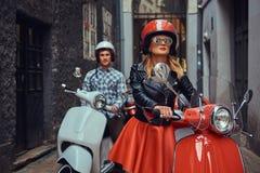 英俊的人和一个性感的时髦的女孩走与沿城市的老街道的减速火箭的意大利滑行车 免版税库存图片