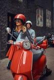 英俊的人和一个性感的时髦的女孩走与沿城市的老街道的减速火箭的意大利滑行车 库存图片