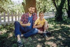 英俊的人和孩子在照相机一起坐草并且看 他们是微笑和看在照相机 bps 免版税库存照片
