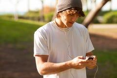 年轻英俊的人咨询的电话户外 免版税库存图片