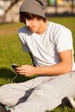 年轻英俊的人咨询的电话户外 免版税图库摄影