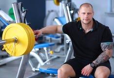 年轻英俊的人在健身房的锻炼以后坐 库存照片