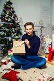 英俊的人在圣诞树附近打开一件礼物在屋子里 n 库存图片