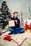英俊的人在圣诞树附近打开一件礼物在屋子里 n 免版税库存图片