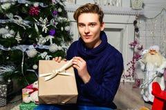 英俊的人在圣诞树附近打开一件礼物在屋子里 n 免版税图库摄影