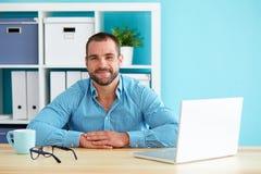 英俊的人在现代办公室 免版税库存图片