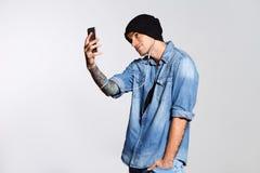 英俊的人在白色墙壁上采取selfie并且smilling 免版税库存照片