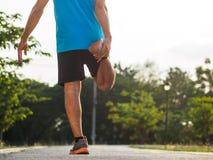 英俊的人在跑步前舒展 健身和生活方式 免版税库存照片