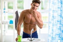 英俊的人在镜子被反射并且检查他的胡子 库存照片