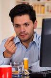 英俊的人在他的手上的拿着一种药片冒泡片剂在办公室 免版税库存图片